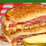 Reuben Sandwich with pickle spear on white plate