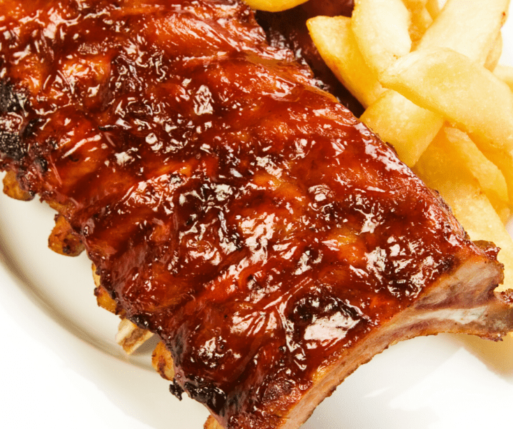 Barbecue Ribs on a white platter with french fries