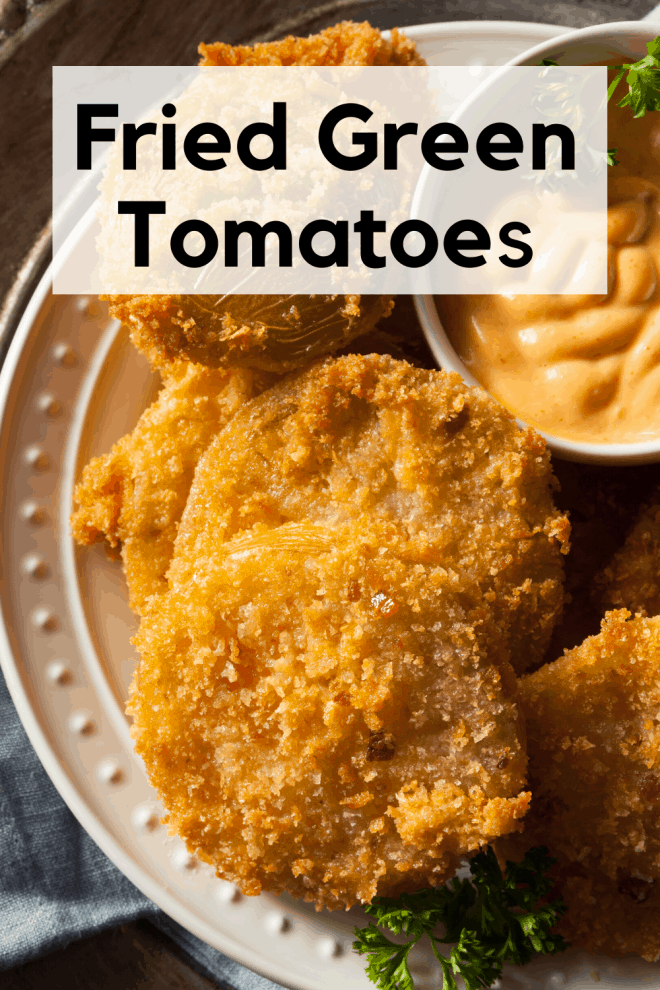 Fried Green Tomatoes on a white plate with a dipping sauce in a bowl on the side