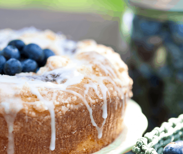 Blueberry Streusel Coffee Cake on white platter topped with fresh blueberries