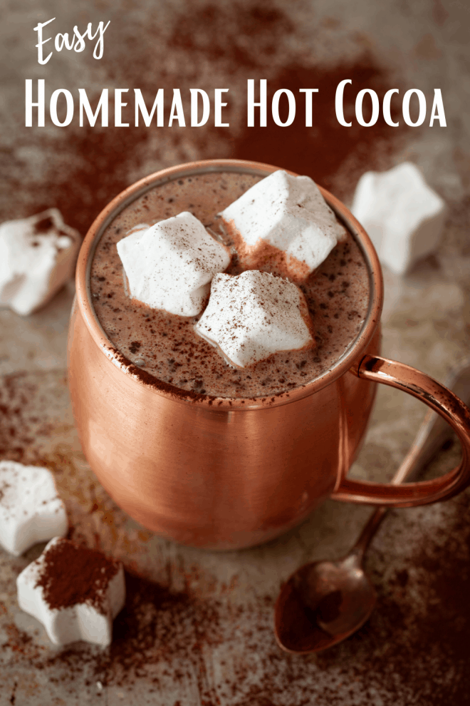 copper mug filled with homemade hot cocoa and topped with star shaped marshmallows and dusted with cocoa powder