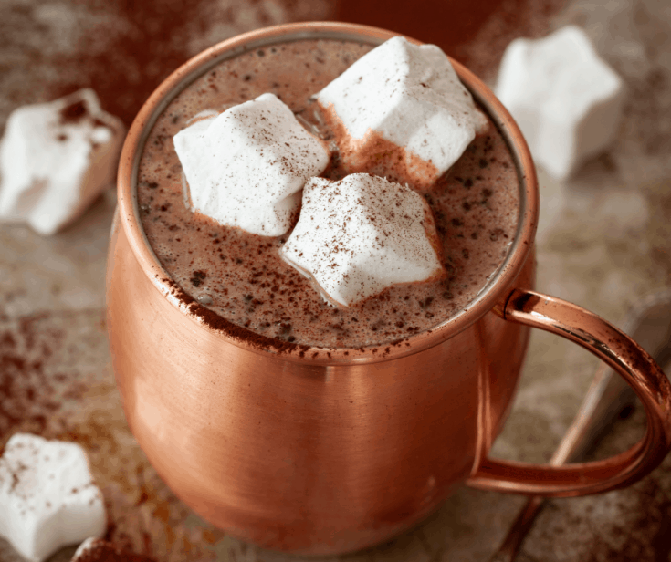 hot chocolate in a copper mug topped with marshmallows