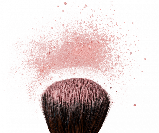 Blush Makeup Tips for Women Over 50 - Large blush brush with blush particles fanning out on white background