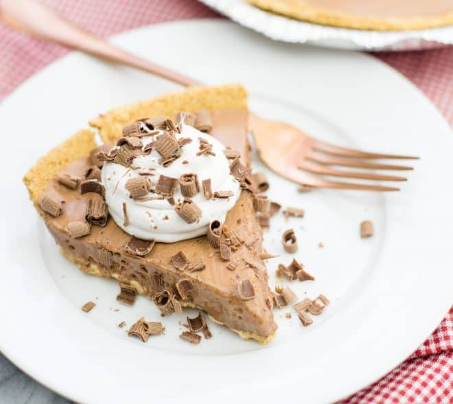 Close Up Photo of Candy Bar Pie on white saucer with fork