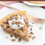 A serving of candy bar pie on a white plate with a fork sitting on a red checked napkin