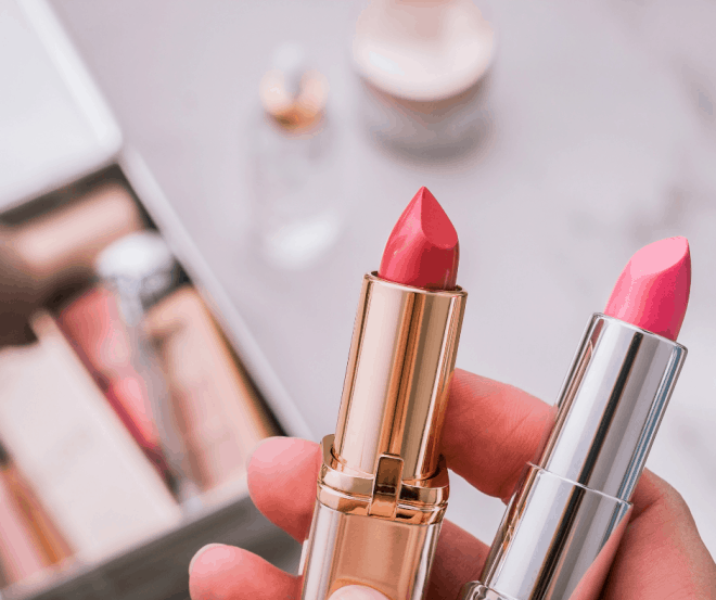 Makeup tips for women over 50 - a hand holding two tubes of pink lipstick