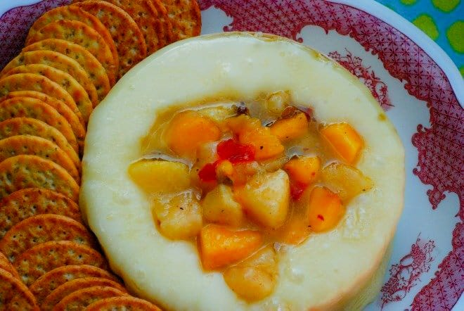 Baked Brie Cheese topped with fresh, diced peaches and hot pepper jelly