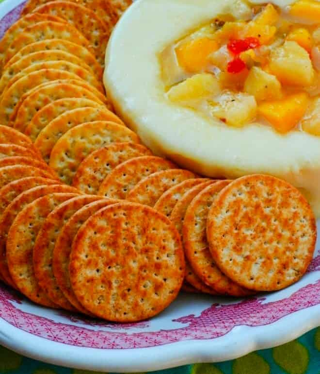 Baked Round Brie topped with a hot pepper jelly and peach topping, in a platter surrounded by round crackers
