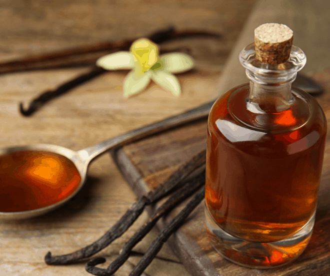Homemade Vanilla Extract With Vanilla Beans and A tablespoon of vanilla on cutting board