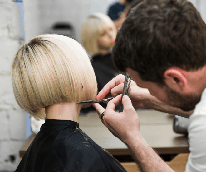 Girl with short blonde hair getting a trim at hairstylist