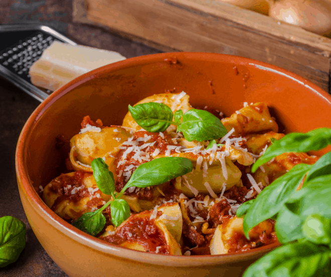 Closeup Photo of Brown bowl filled with tortellini covered in a red cheese sauce