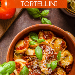 Spinach and Cheese Filled Tortellini topped with a red sauce and garnished with basil leaves