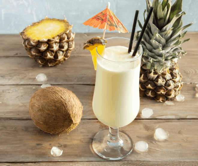 Breakfast Pina Colada Smoothie surrounded by coconuts and pineapples