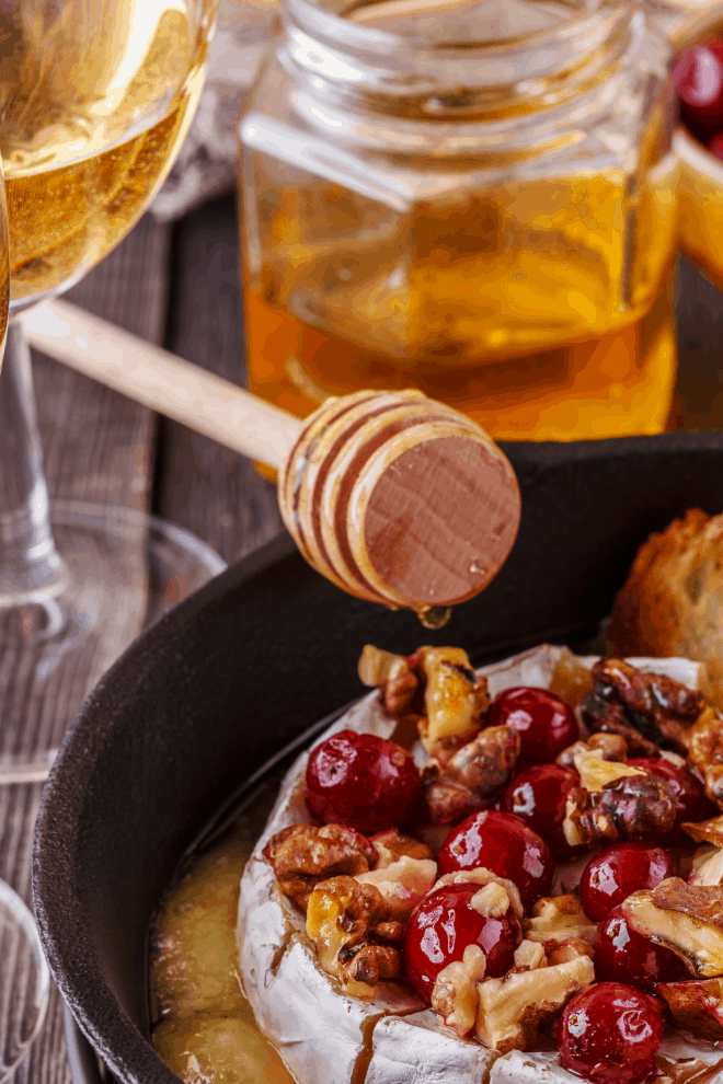 Brie Cheese Drizzled with honey, cherries and walnuts in a black serving dish