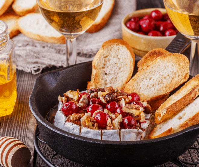 Platter with baked brie drizzled with honey and topped with walnuts with baguette slices