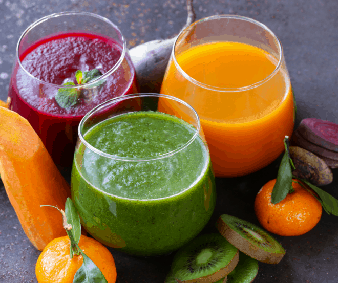 Fresh vibrant colored green juice, orange juice and beet juice in small glasses