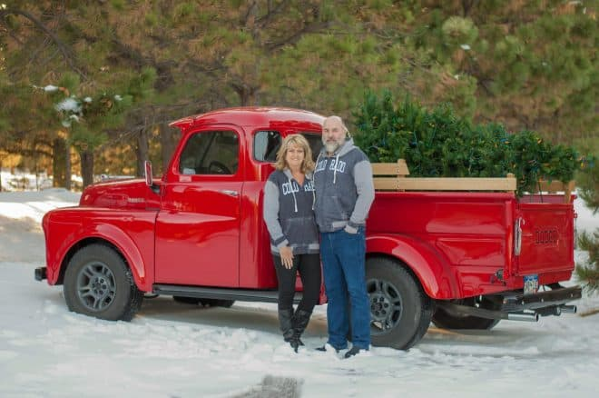A couple standing in front of a red truck