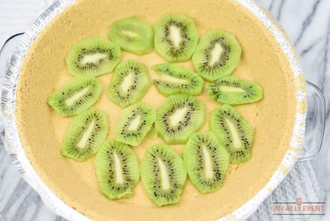 No Bake Kiwi Pistachio Pie - Line pie crust with sliced kiwi fruit.