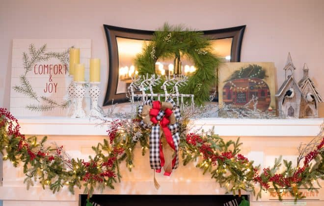 Lighted Green Garland With Buffalo Plaid Bows are on a mantle for decoration
