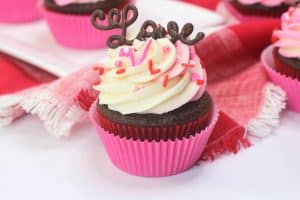 One Cupcakes In Pink Wrapper Topped with Pink and White Frosting and Sprinkles