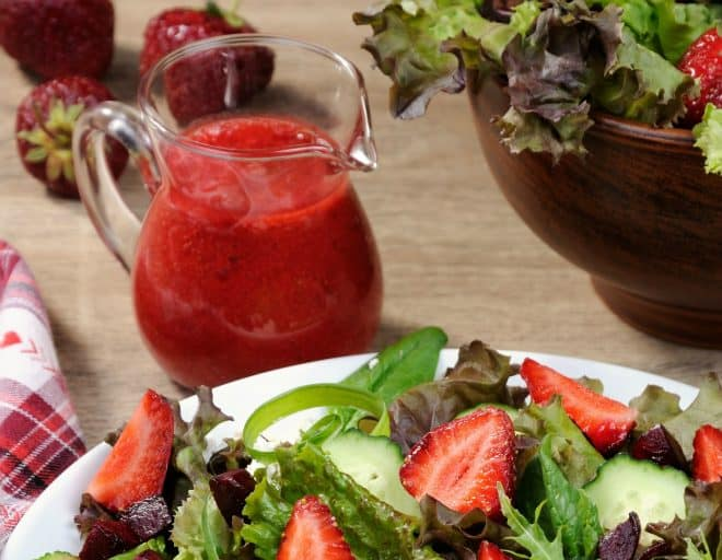 Salad on white dish and strawberry vinaigrette in small pitcher
