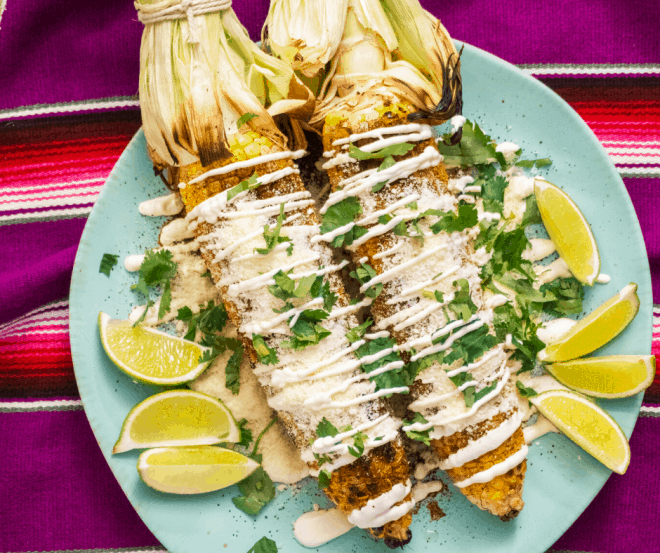 Mexican Street Corn on blue plate with limes and sour cream mixture