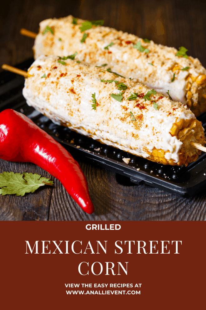 Grilled Mexican Street Corn on black dish with red peppers