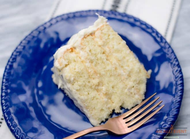 A slice of a three layered coconut cake with cream cheese coconut frosting