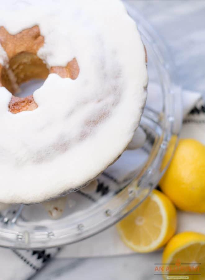 Lemon Pound Cake on Glass Cake Plate and three lemons on the side