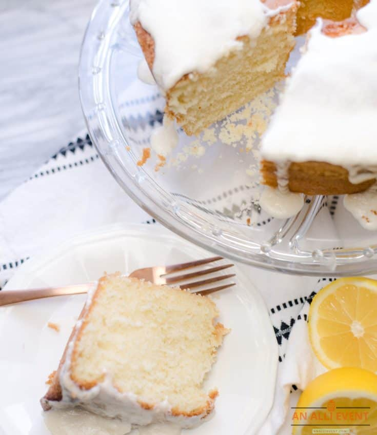 A slice of lemon buttermilk pound cake on white plate with gold fork