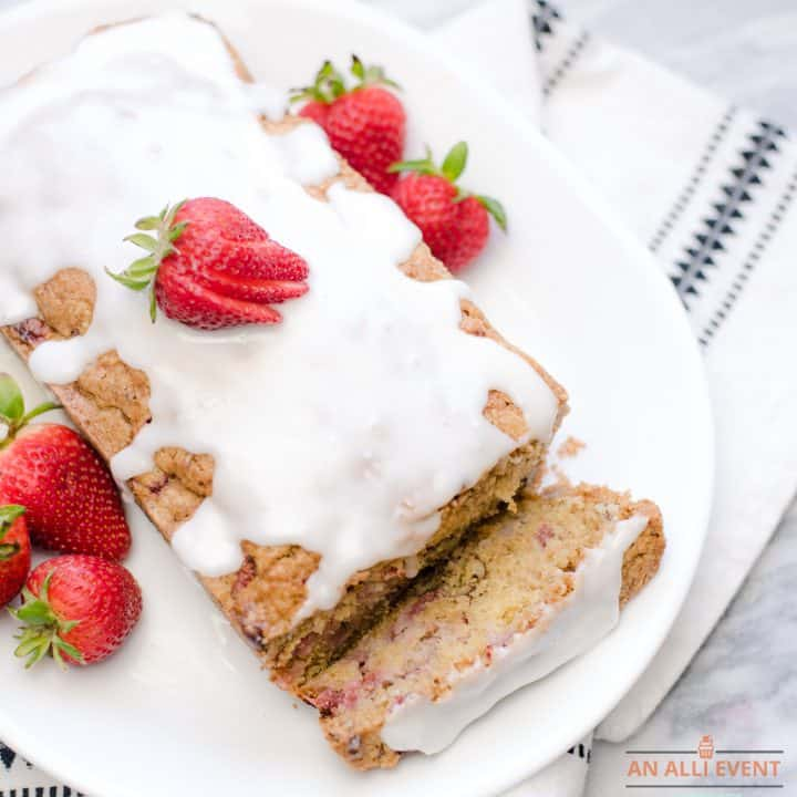 A loaf of strawberry bread with a white glaze on a white platter - garnished with fresh strawberries