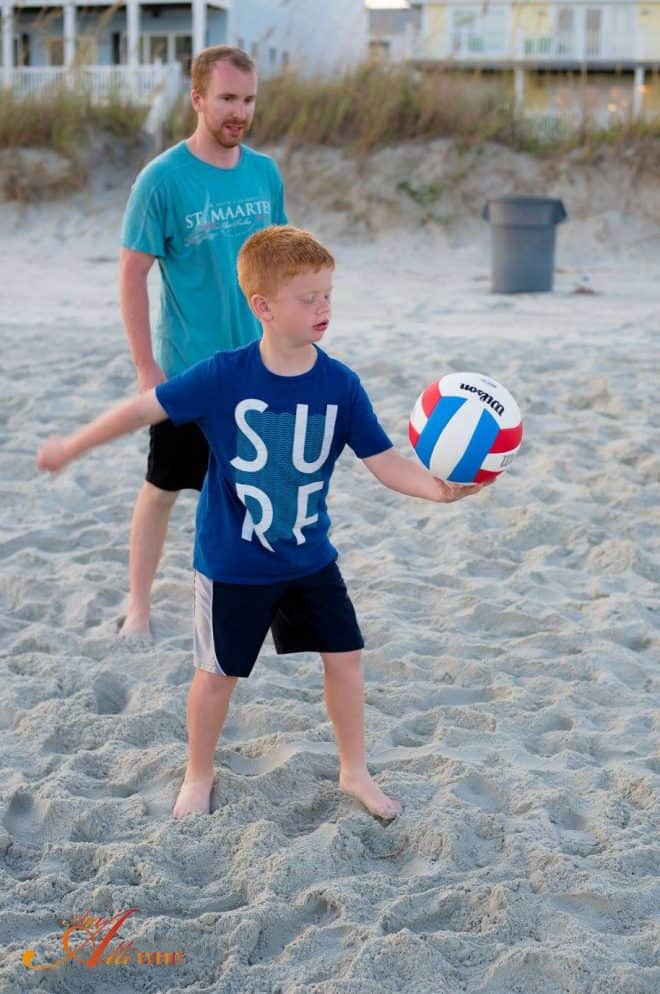 Child playing volleyball on beach