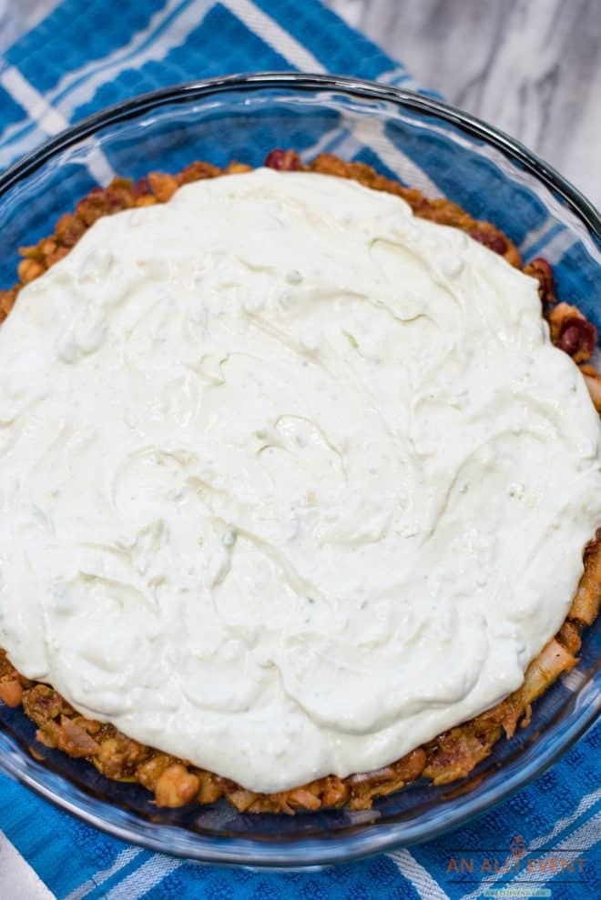 Five Bean Salad Layer topped with a cream cheese and sour cream mixture placed in a glass pie pan