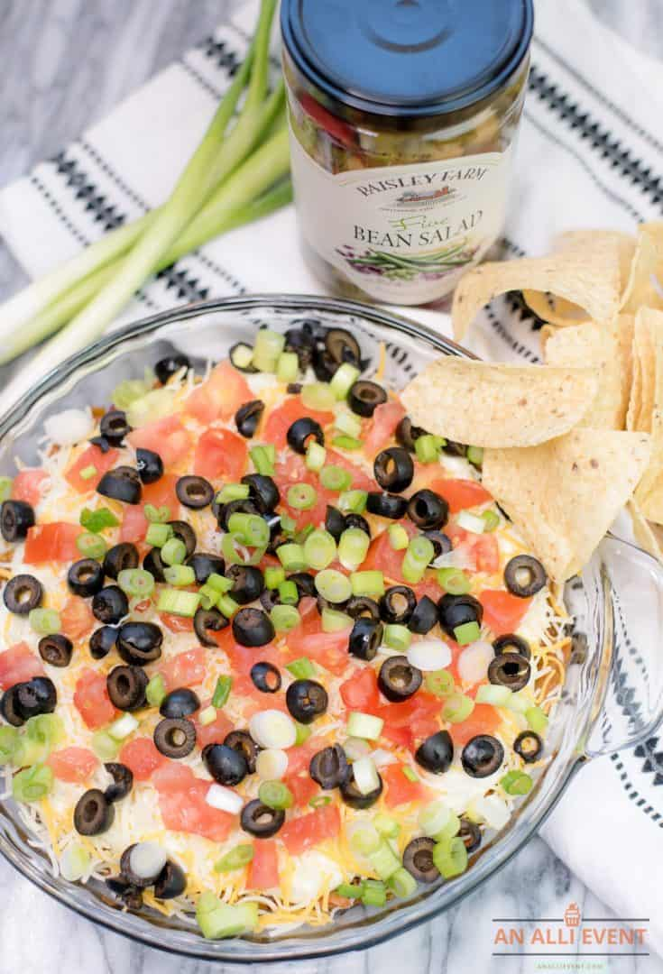 Bean Salad Taco Dip in a glass plate topped with chopped tomatoes and sliced black olives