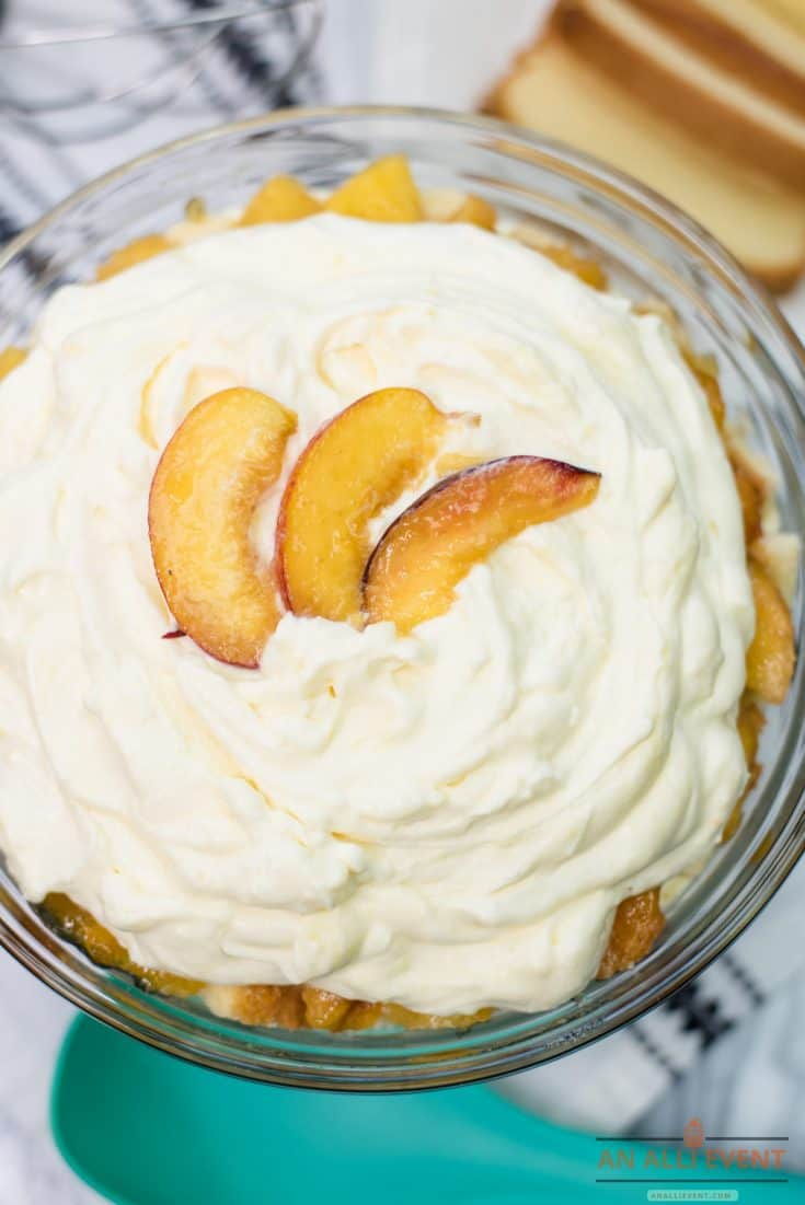 Layered Peaches and Cream Trifle in glass bowl, garnished with sliced peaches