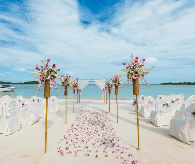 wedding ceremony on sandy beach with flowers