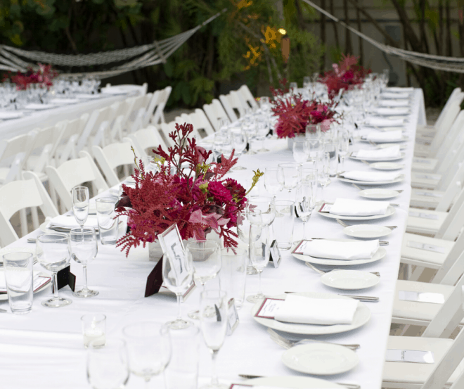 Long Table With White Tablecloth, white china and red flowers