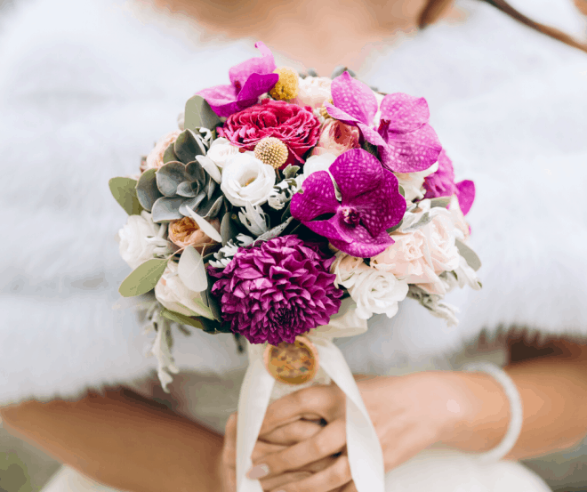 bride holding a bouquet of pink, purple, white and green flowers