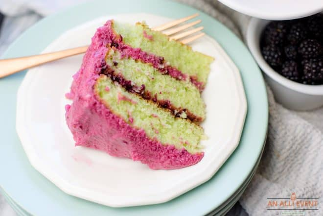 Slice of 3-layer blackberry lime cake with blackberry coulis and blackberry buttercream