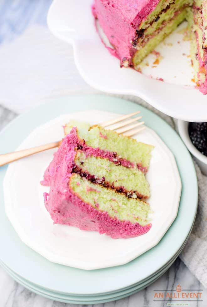 Blackberry Lime Cake With Blackberry Coulis and Blackberry Buttercream on a white dessert plate