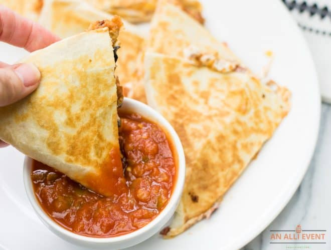 Taco Salad Dip Quesadillas dipped in salsa on white platter