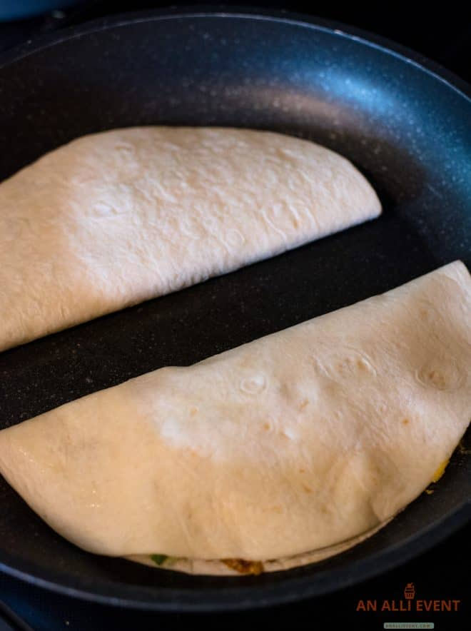 two folded quesadillas in a skillet cooking
