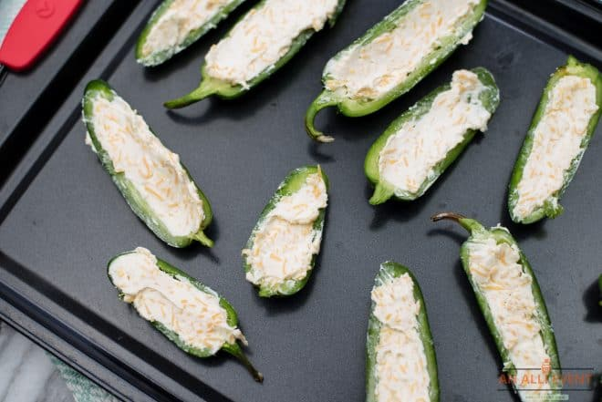 Jalapeno Poppers stuffed with cheese and wrapped in bacon on platter