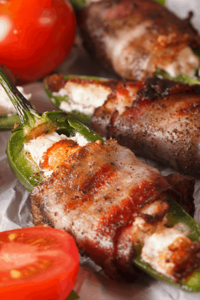 Baked Bacon-Wrapped Jalapeno Poppers with red tomatoes on a plate