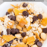 Tropical Macadamia Nut Trail Mix in white bowl. It includes milk chocolate chips, mango and coconut.