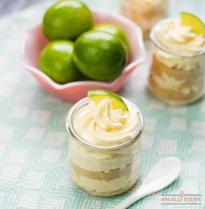 Layered Lime Cheesecake Pudding Parfaits in front of limes in pink bowl