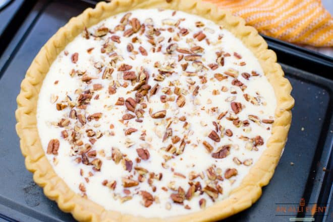 Chopped pecans sprinkled over cream cheese layer in pineapple pie