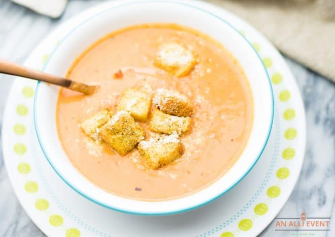 tomato soup in white bowl, topped with croutons and grated parmesan cheese