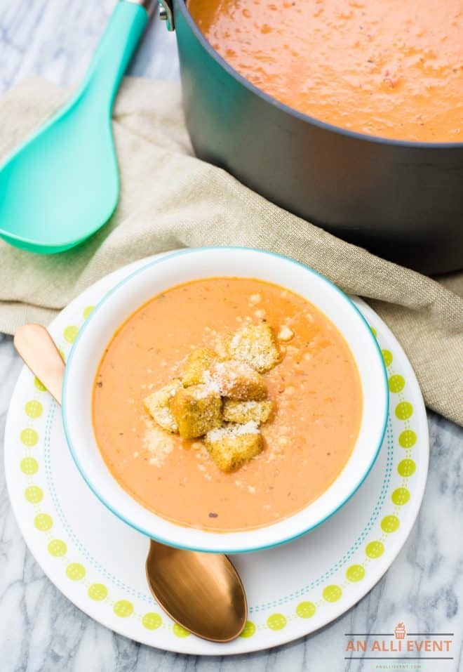 Tomato Soup topped with croutons and cheese, served in a white bowl