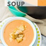Homemade Tomato Soup is white bowl topped with croutons and sprinkled with parmesan cheese